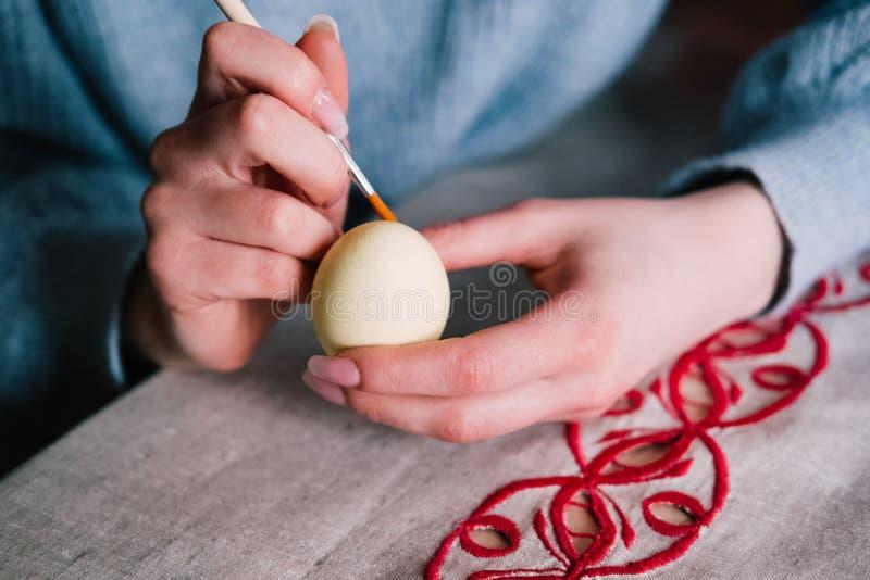与刷子的女性手绘画复活节彩蛋 图库摄影