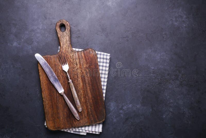 与切板和亚麻布餐巾葡萄酒叉子和刀子拷贝空间的黑暗的石桌 库存图片