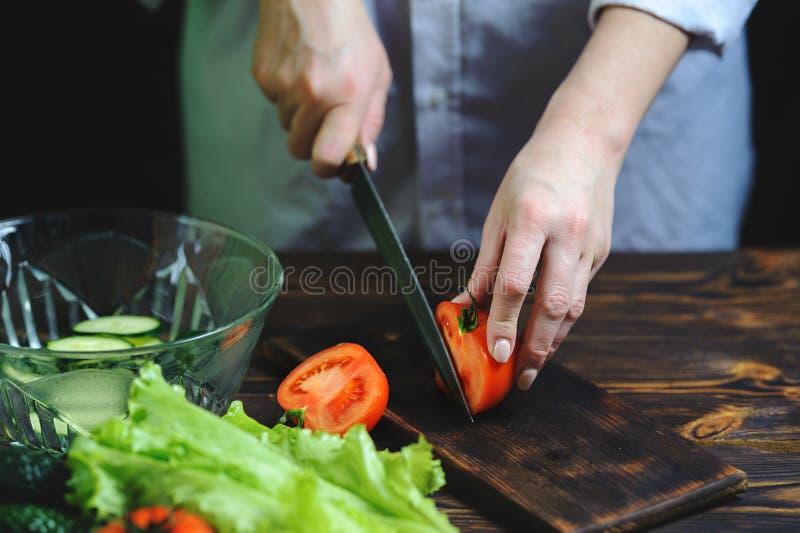 与刀子的厨师裁减蕃茄特写镜头 库存照片
