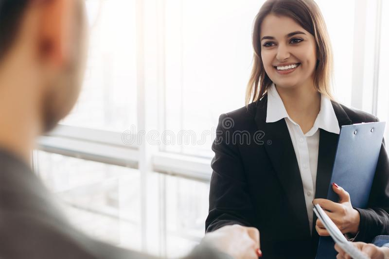 与商人的微笑的有吸引力的女实业家握手在宜人的谈话,好关系以后 企业概念照片 免版税库存照片