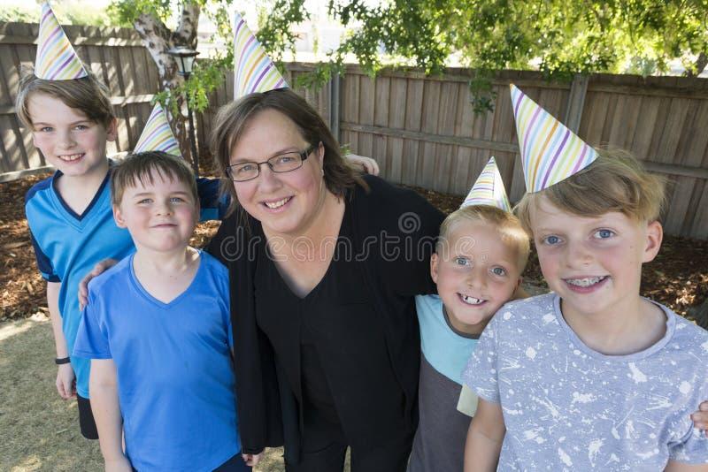 与四个男孩的一个生日姿势 图库摄影