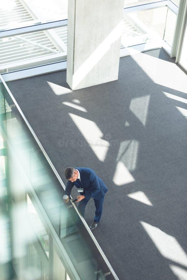 与咖啡杯的商人使用在办公楼的手机 免版税图库摄影