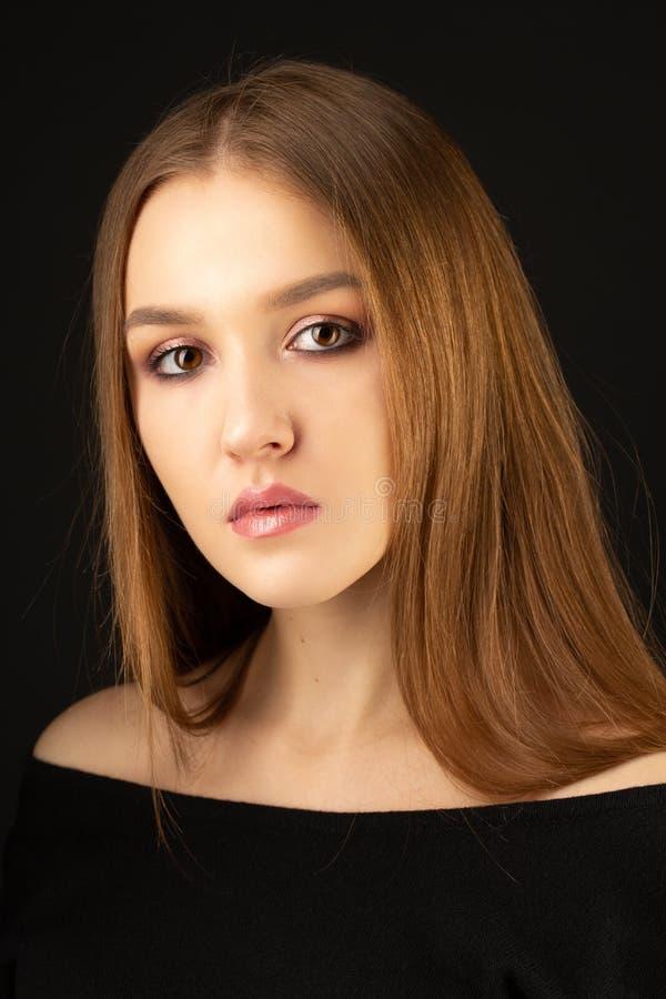与桃红色光滑的构成的美好的白肤金发的模型在黑背景 免版税库存图片