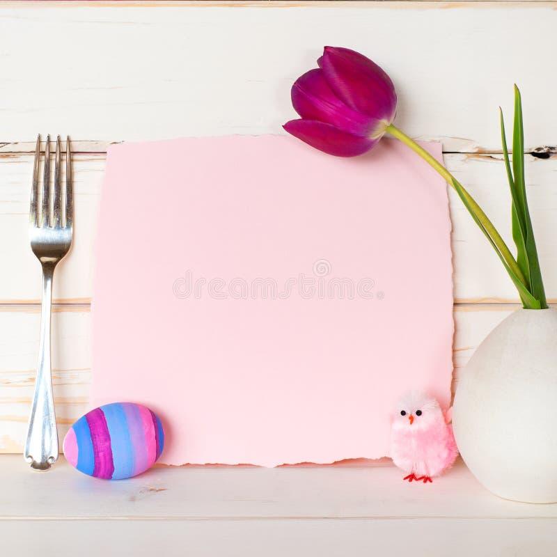 与桃红色晚餐会的复活节快乐邀请与一把逗人喜爱的小鸡、紫色郁金香花、鸡蛋和叉子的卡片在现代静物画Arrangem 免版税库存照片