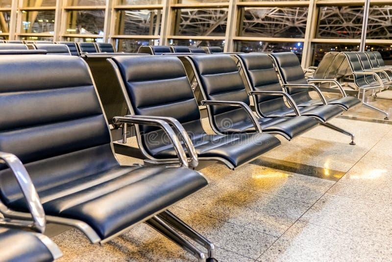 与椅子的空的机场终端等候室在晚上,旅行概念 免版税库存照片