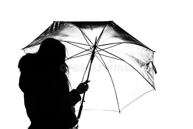 与模型的美丽的背后照明在剪影的一把开放伞下 免版税库存图片