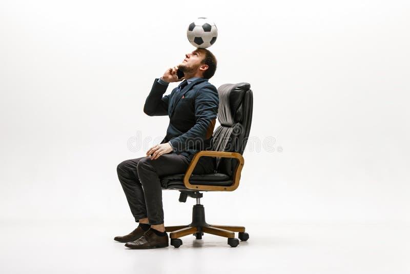 与橄榄球球的商人在办公室 库存照片
