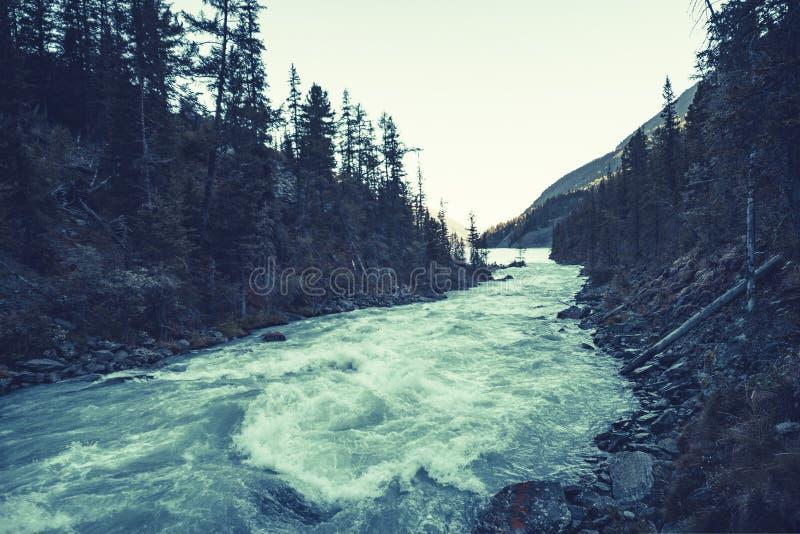 与河的阴沉的山风景相反银行的 河石河岸  水的深绿颜色 令人毛骨悚然的大气 库存图片