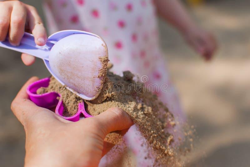 与沙子的模子在手上 图库摄影