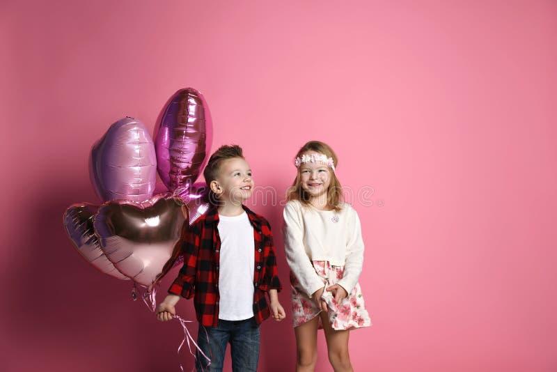 与淡色气球的小男孩和女孩孩子为情人节或生日在背景与大方的本体空间 库存图片