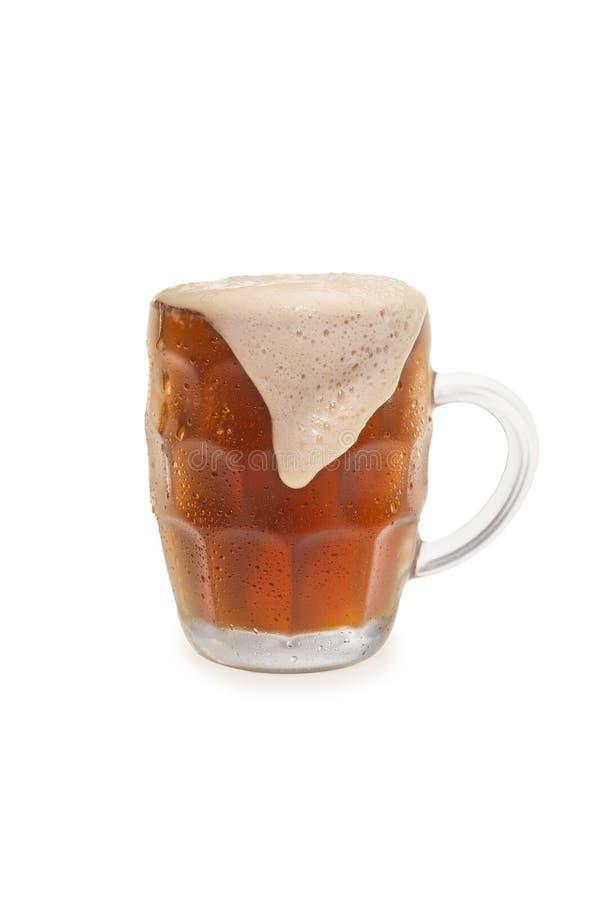 与溢出的泡沫上面的浓味啤酒 库存照片