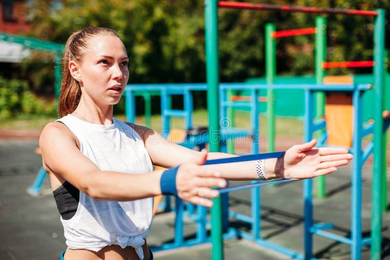 与抵抗带的健身年轻女人背部锻炼训练力量的 女性athete行使 免版税库存图片