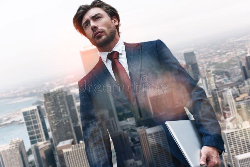 与技术的信心 英俊的商人藏品膝上型计算机画象,当站立反对早晨时 库存照片