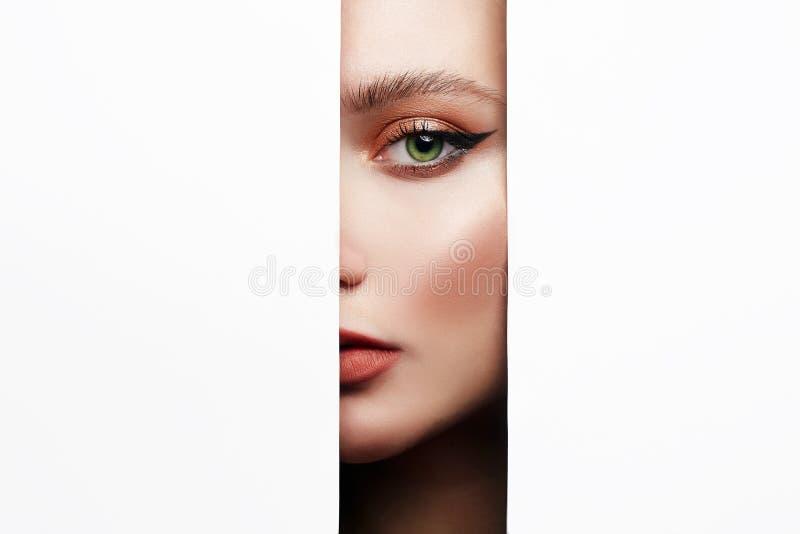 与构成的女性面孔到纸孔里 库存图片