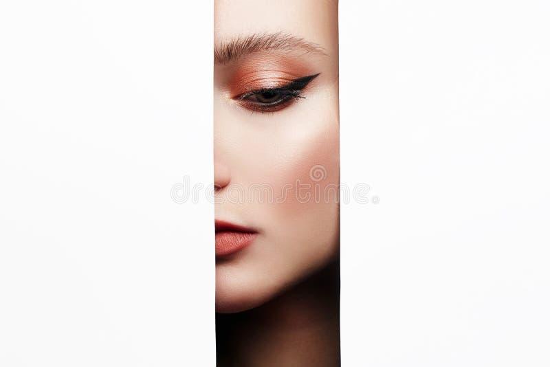 与构成的美丽的女性面孔到纸孔里 免版税库存图片