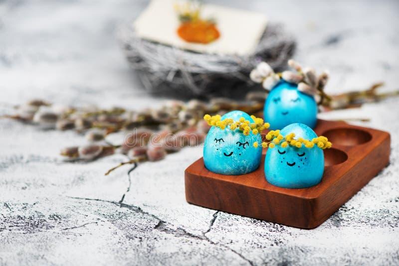与春天花花圈的复活节蓝色鸡蛋  库存照片