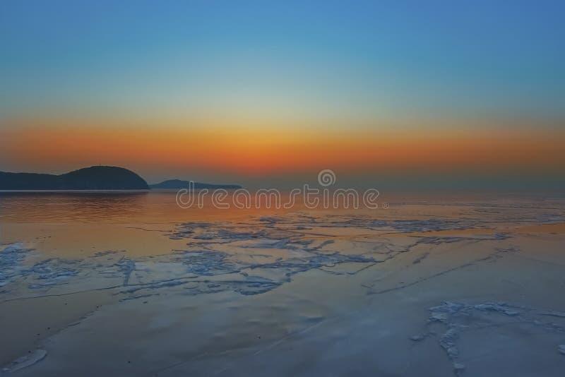 与明亮的橙色日落和冰川的海景在海岸线 免版税图库摄影