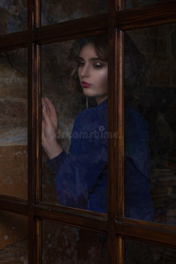 与摆在玻璃门后的卷发佩带的女衬衫和项链的魅力深色的模型 免版税库存图片