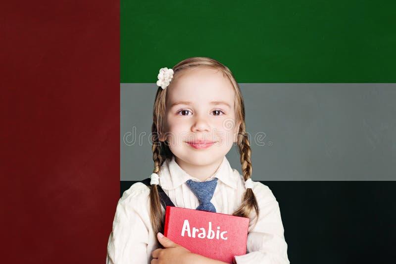 与愉快的儿童女生的阿拉伯联合酋长国概念有反对阿拉伯联合酋长国旗子背景的红色书的 库存照片