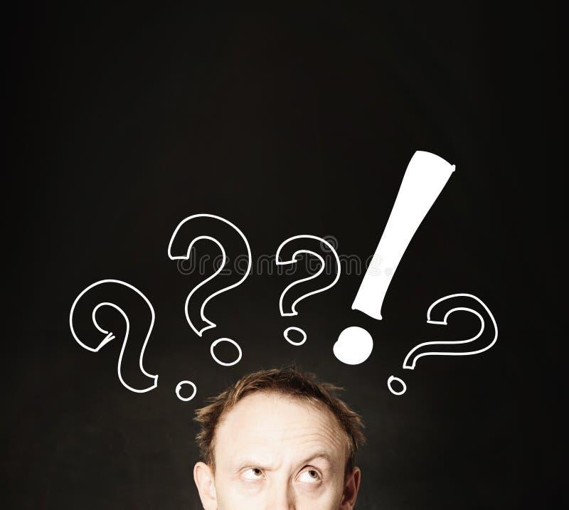 与手图画问号的滑稽的人面孔在黑板背景 免版税库存照片