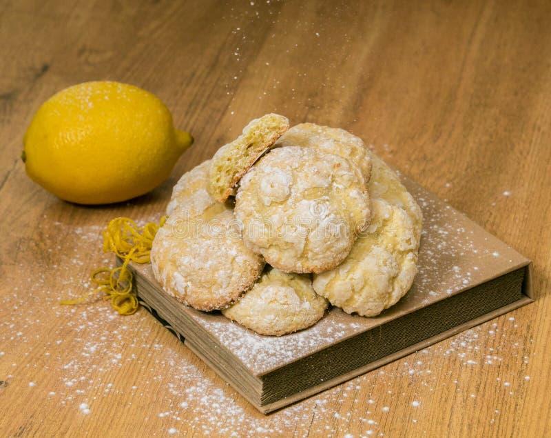 与新鲜的柠檬和果皮特写镜头的自创柠檬糖屑曲奇饼在木背景 库存图片