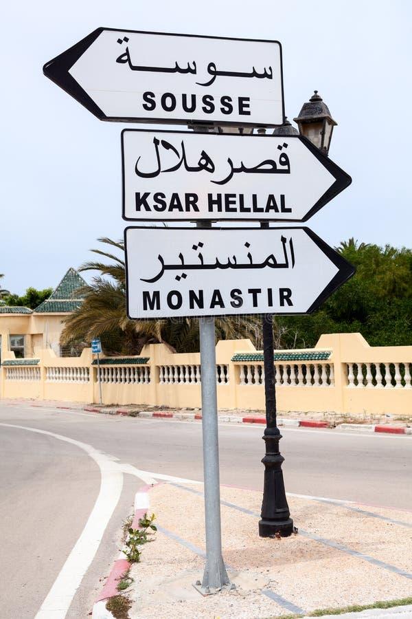 与方向的路标到莫纳斯蒂尔、苏斯和Ksar Hellal在突尼斯的镇 英国和阿拉伯题字 闹事 库存图片