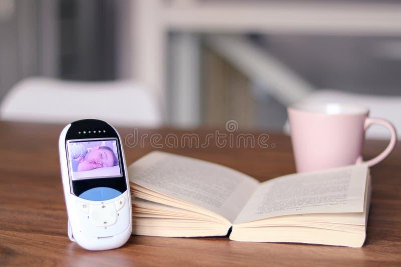 与睡觉的婴孩的图象的录影婴孩显示器在屏幕上的在与开放书和茶杯子的桌上 在池氏期间,母亲放松时间 库存照片