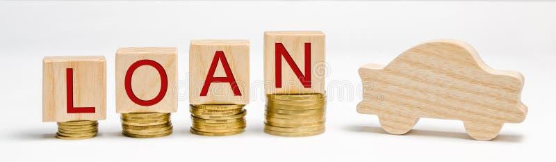 与硬币的木块和词贷款和汽车 买在信用的一辆汽车的概念 汽车的债务 通信工具 的treadled 免版税库存照片