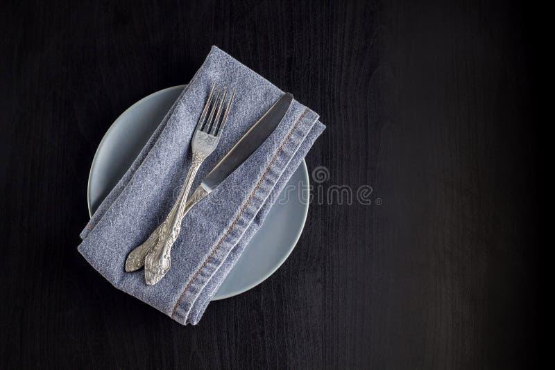 与空的板材餐巾叉子的桌在黑背景的设置和刀子 免版税库存图片