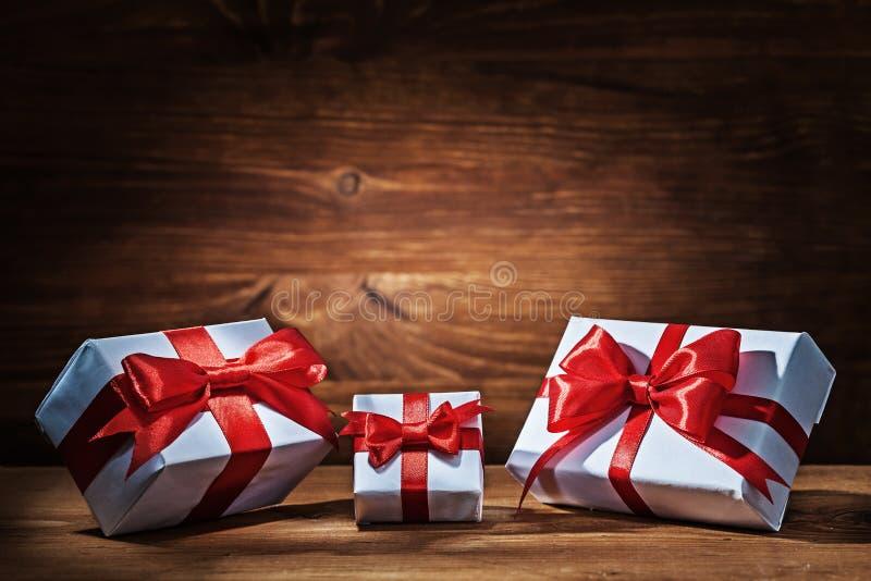 与红色丝带的Giftboxes在葡萄酒木头 库存图片