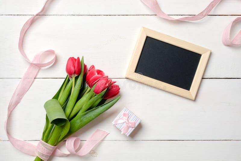 与红色郁金香花的空白的贺卡在白色木桌上 浪漫喜帖、贺卡妇女的或母亲节, 免版税库存图片