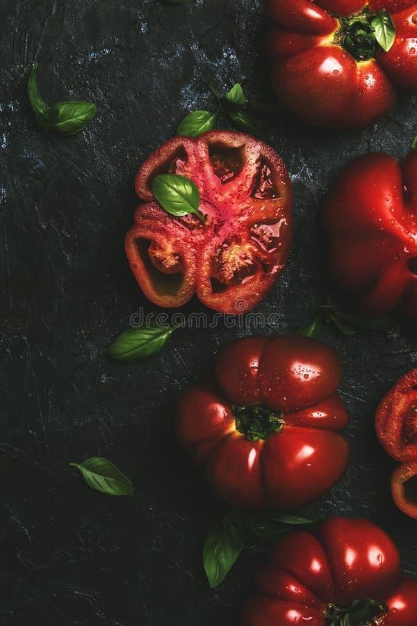 与绿色蓬蒿叶子在黑厨房用桌背景,夏天收获的红色蕃茄,烹调沙拉,顶视图 库存图片