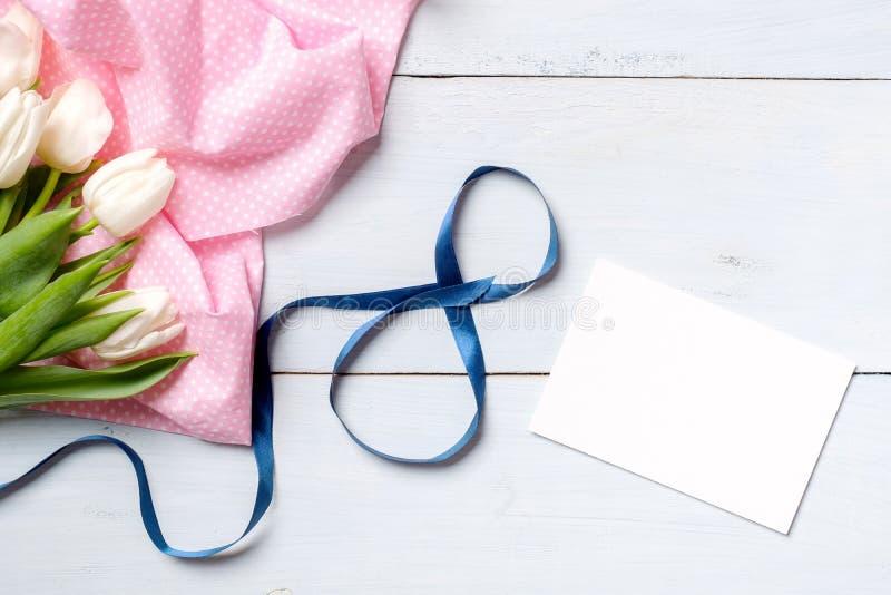 与美丽的弯曲的丝带,束郁金香花,空插件的8次行军背景 平的位置,在看法上 免版税库存照片