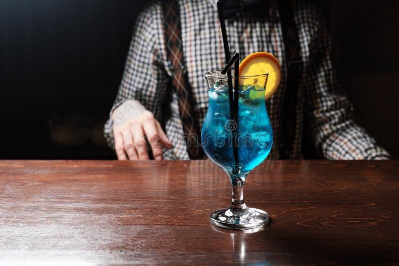 与石灰、冰和薄菏的蓝色库拉索岛鸡尾酒在木背景的马蒂尼鸡尾酒玻璃 免版税库存图片