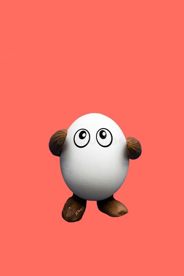 与眼睛、胳膊和腿的赋予生命的滑稽的鸡鸡蛋 免版税库存图片