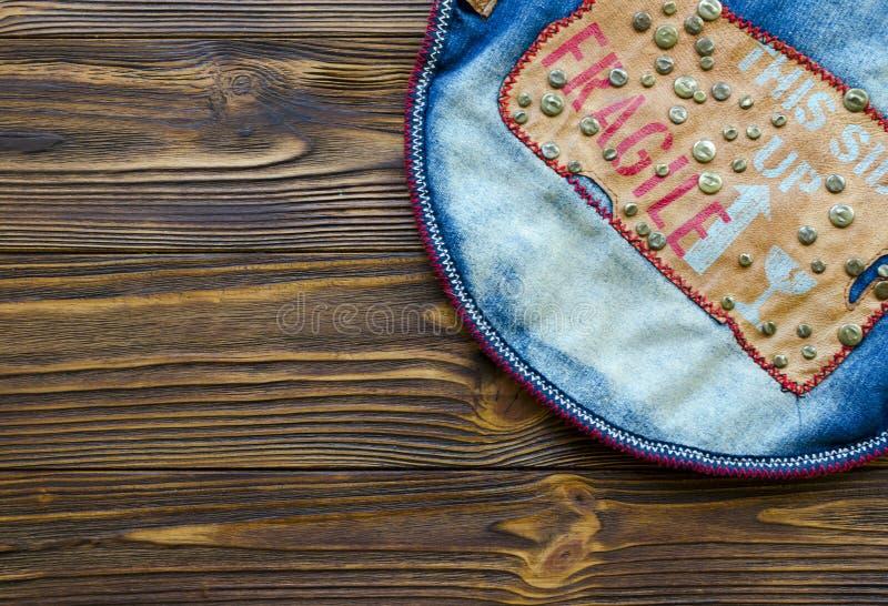 与皮革条纹和金属铆钉的牛仔裤牛仔布在木桌上 免版税库存图片