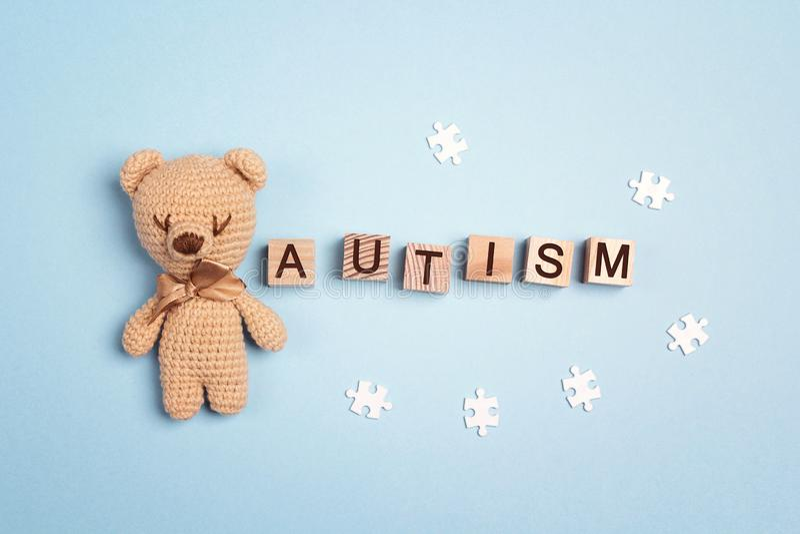 与玩具熊的孤独性在木立方体的概念和词在蓝色背景 孤独性了悟天 库存照片