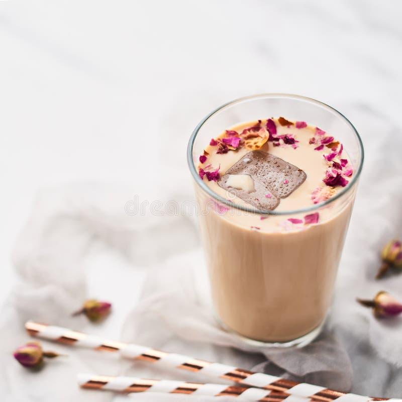 与玫瑰和豆蔻果实的冰冻咖啡在一块高玻璃 免版税图库摄影