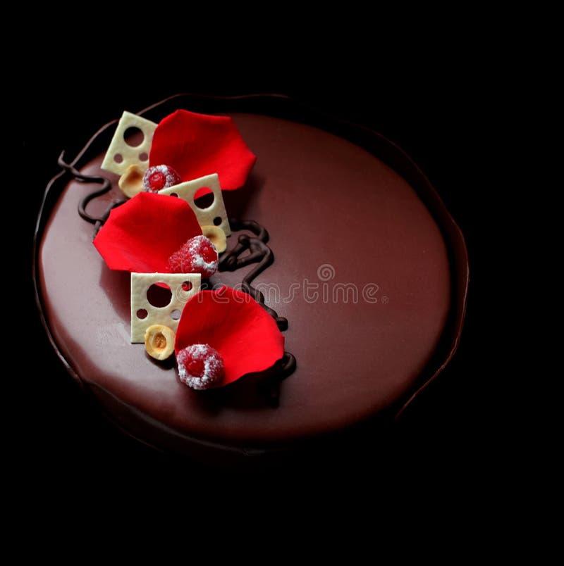 与玫瑰花瓣和白色巧克力装饰的浪漫巧克力蛋糕 免版税库存照片