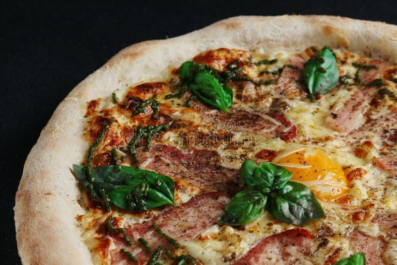 与烟肉和鸡蛋关闭的Carbonara比萨在黑暗的背景 库存图片