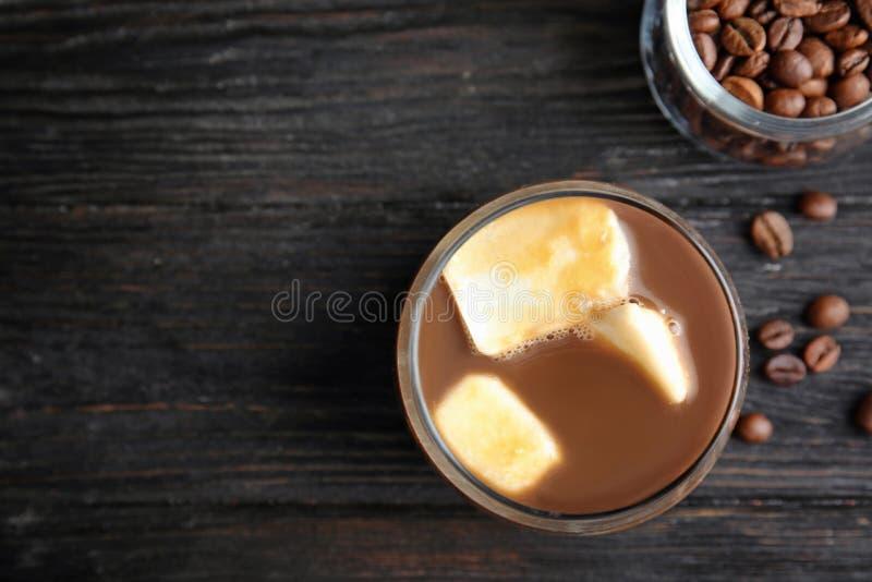 与牛奶冰块和豆的咖啡饮料在黑暗,平的位置 文本的空间 库存图片
