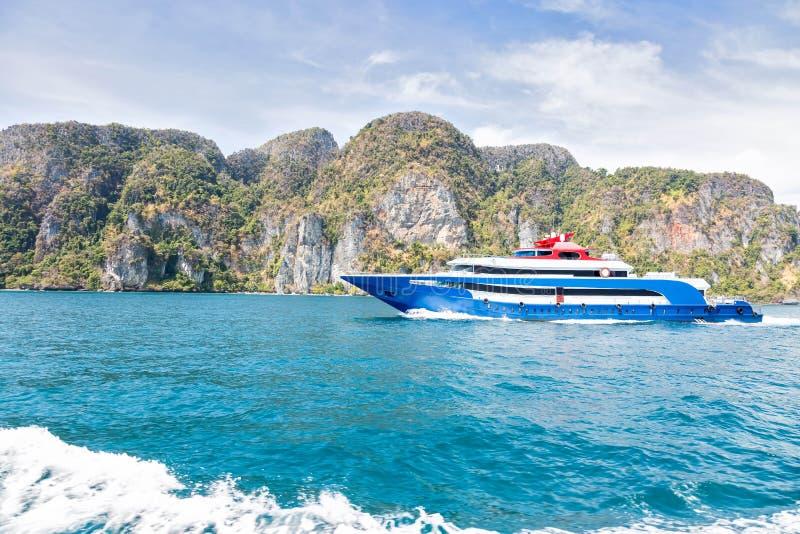 与白色和红色口音乐趣速度小船的蓝色 在海的航行反对一个热带山海岛 侧视图 马达轨道 库存照片