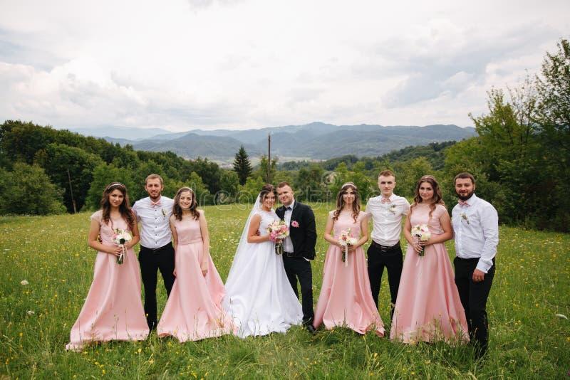 与男傧相和女傧相的新郎和新娘立场 亲吻与朋友的新婚佳偶 衣物夫妇日愉快的葡萄酒婚礼 背景  免版税库存照片