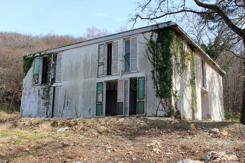 与破裂的部分地长满与履带牵引装置植物和被围拢的门面和残破的窗口的老被放弃的小旅馆大厦 免版税库存照片