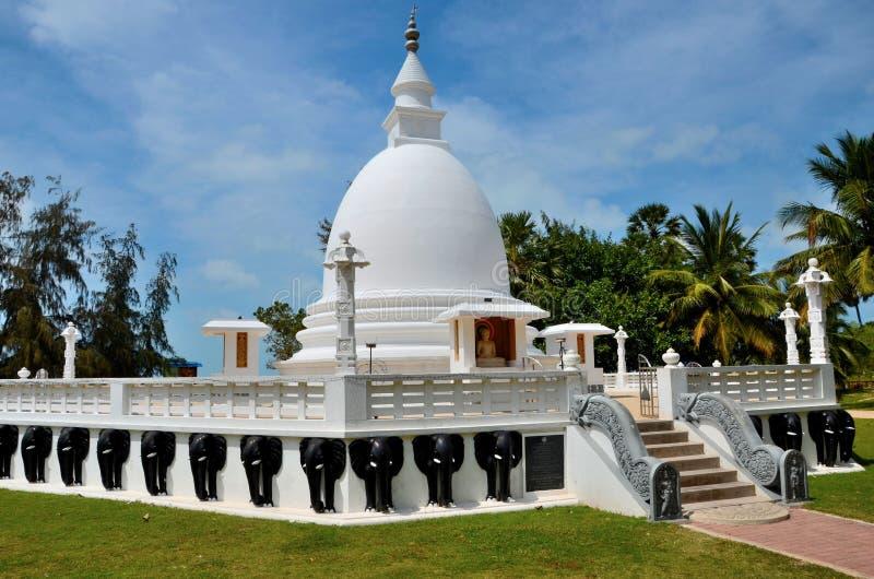 与菩萨雕象的佛教stupa在Dambakola Patuna僧伽蜜多寺庙复杂贾夫纳斯里兰卡 免版税库存图片