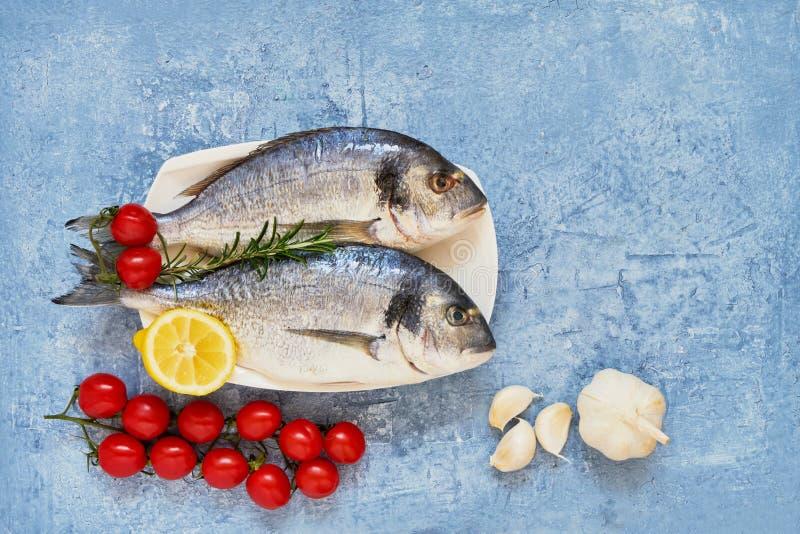 与菜的新鲜的皇家Dorada在蓝色背景 健康概念的食物 顶视图,拷贝空间 免版税库存照片