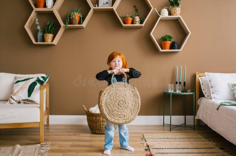 与袋子和微笑的滑稽的矮小的白种人红头发人女孩身分 库存照片