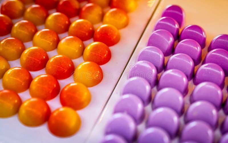 与西番莲果ganache中心和白色块菌状巧克力的白色巧克力壳充满乳脂状的蔓越桔 巧克力 库存照片