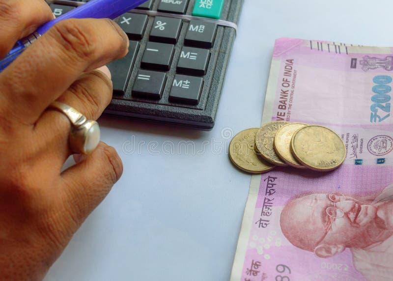 与计算器和拿着一支笔的妇女支票账户与印度货币笔记硬币 簿记员妇女或财政审查员 库存照片