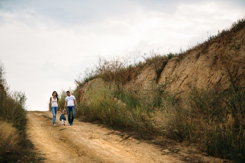 与走在乡下公路的一个小孩子的年轻家庭,户外背景 免版税库存照片